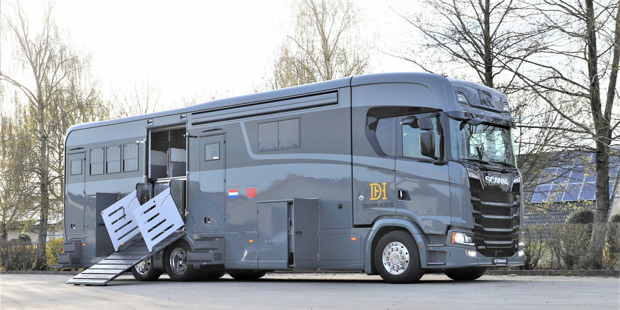 Een grijze paardenvrachtwagen van het merk Scania met optische zwarte lijn gebouwd door Krismar horse trucks.