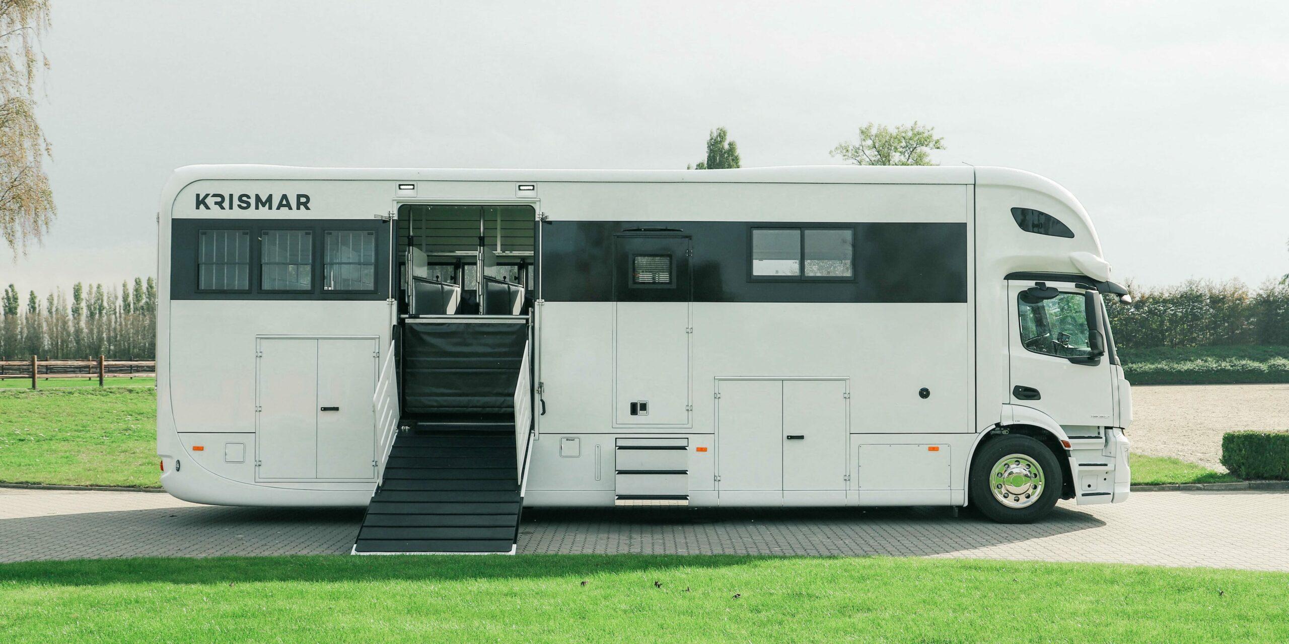 Zijkant van een witte Krismar paardenvrachtwagen voor 5 paarden met ruime leefruimte.