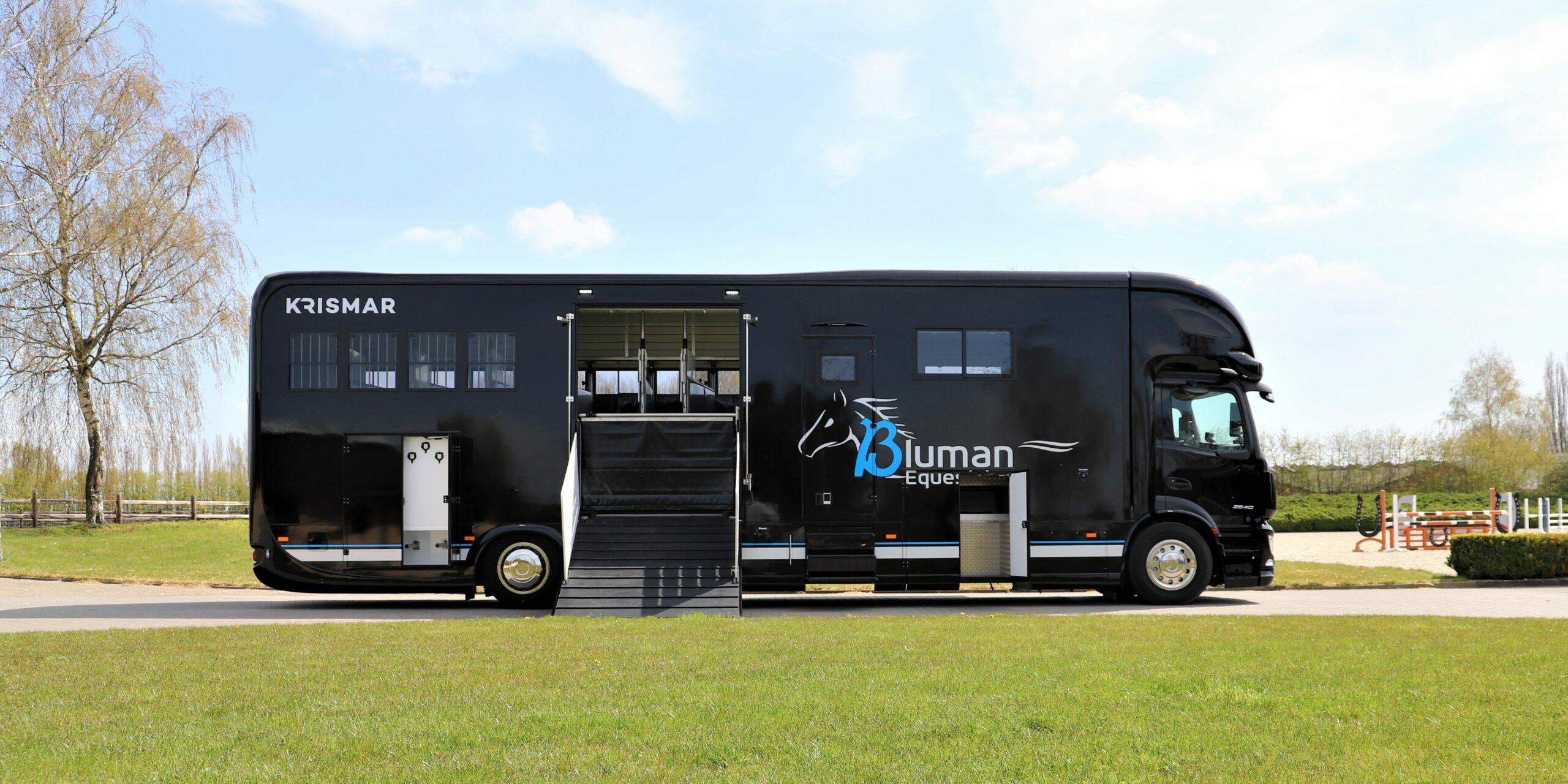 Een zwarte paardenvrachtwagen met logo van Bluman Equestrian